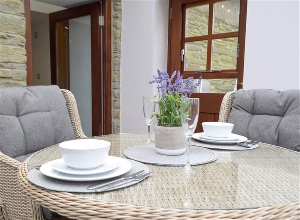 Sun room/dining area with patio doors leading to garden at Snowdrop Cottage,