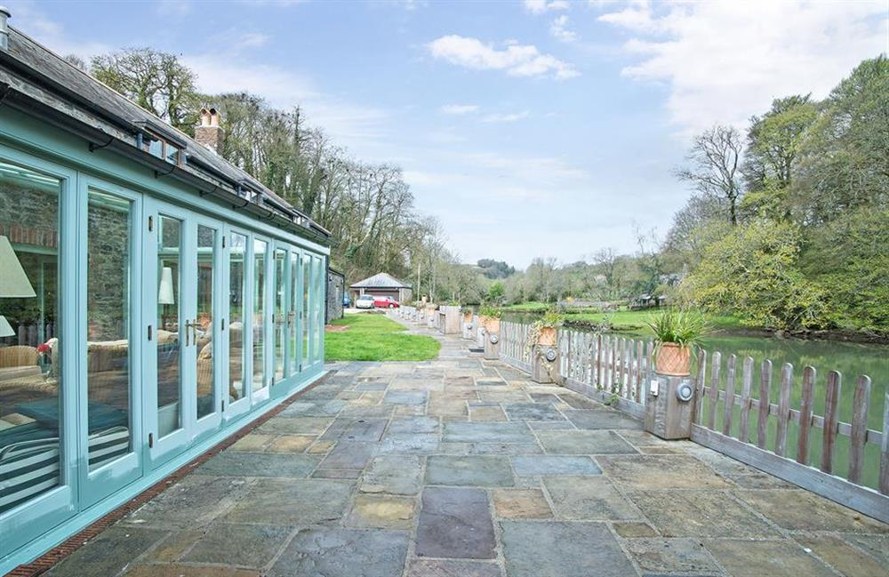 The waterside terrace, furnished with garden table and chairs at Perchwood Shippon, Tuckenhay
