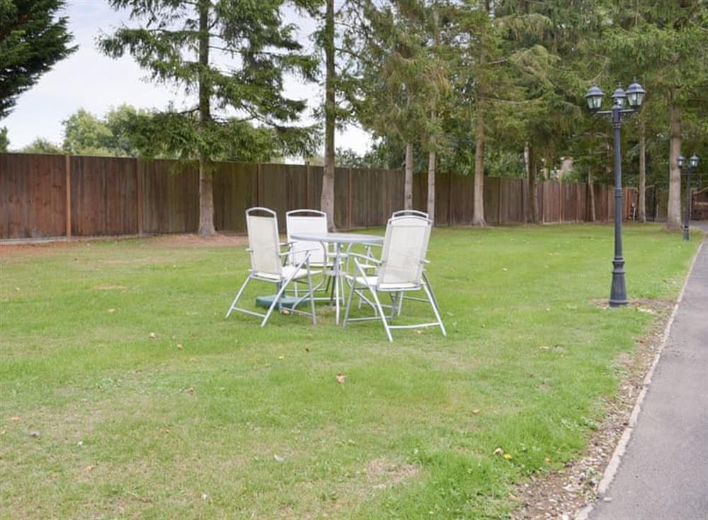 Lawned garden area with garden furniture at Pinewood Cottage in Hainford, near Norwich, Norfolk