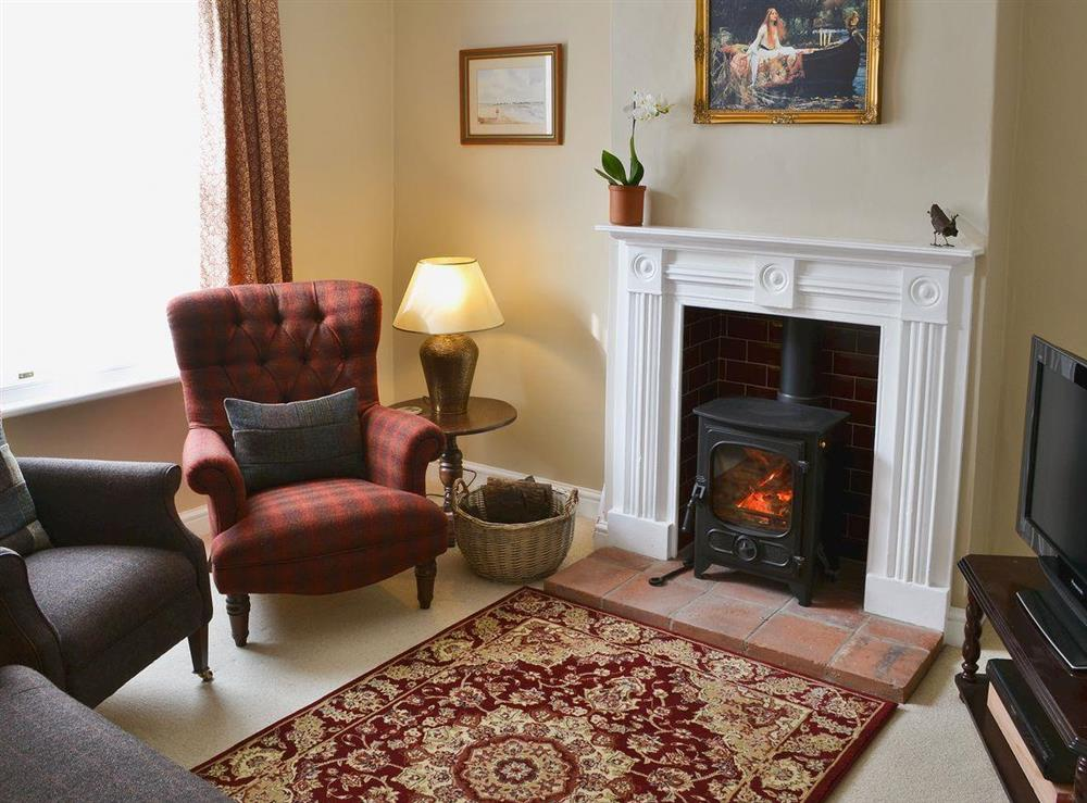 Living room with wood burning stove at Pippin Cottage in Holt, Norfolk
