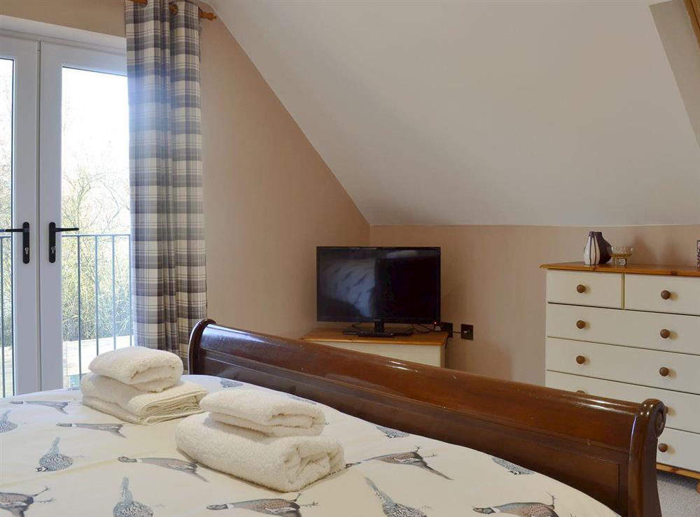 Comfortable double bedroom with Juliet balcony at Quarry Lodge in Munsley, near Ledbury, Herefordshire