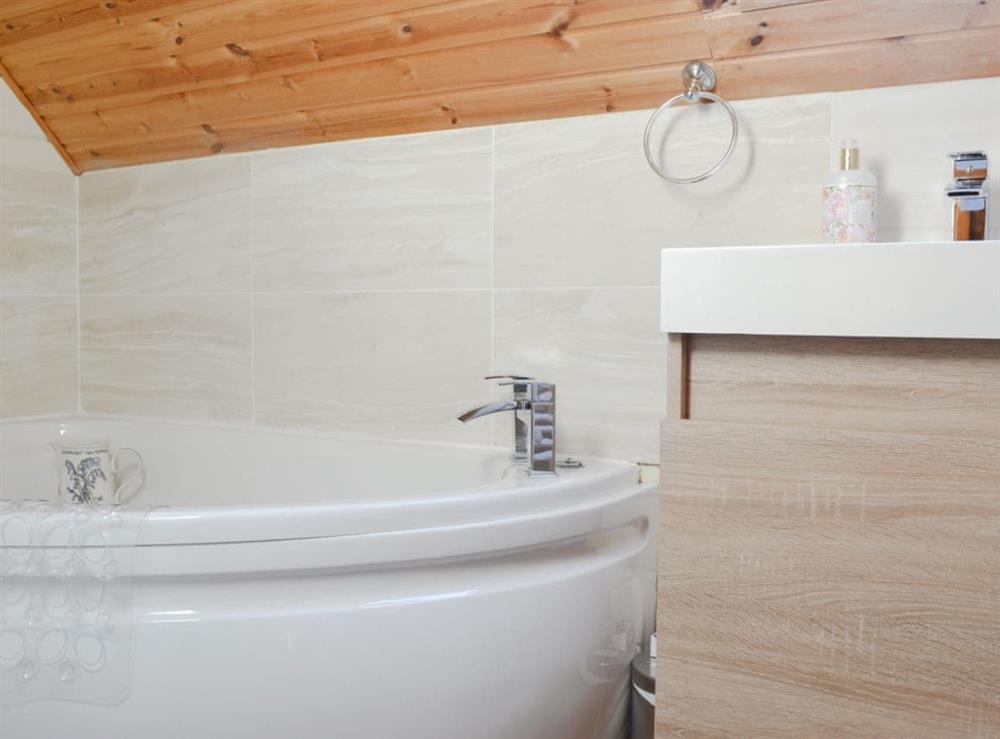 En-suite bathroom with corner bath at Quarry Lodge in Munsley, near Ledbury, Herefordshire