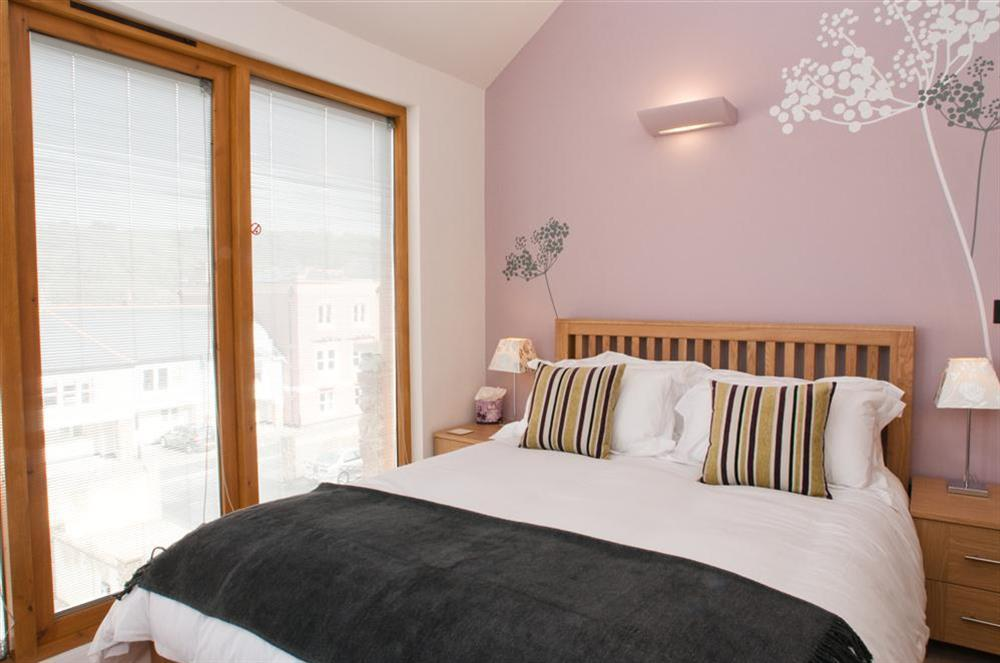 Master bedroom with King-size bed and doors to balcony at Quay Lodge in 60 Sandquay Road, Dartmouth