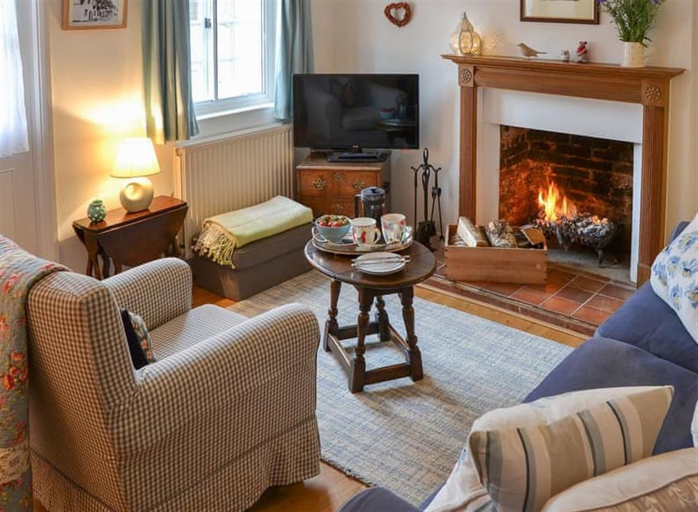 Cosy living room with open fireplace at Red Brick Cottage in Lavenham, Suffolk