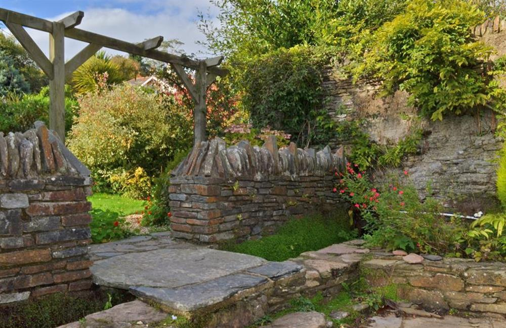 The stone bridge over the shallow stream from courtyard to garden at Rill House, Slapton