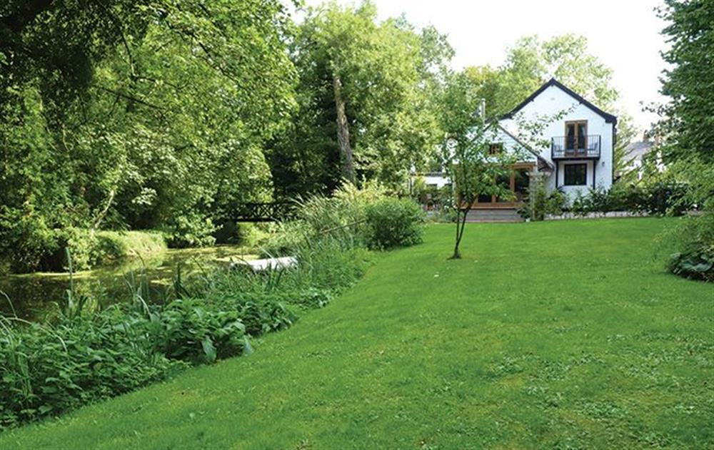 Enclosed garden with seating overlooking the river at Riverside Cottage (Suffolk), Old Water Mill