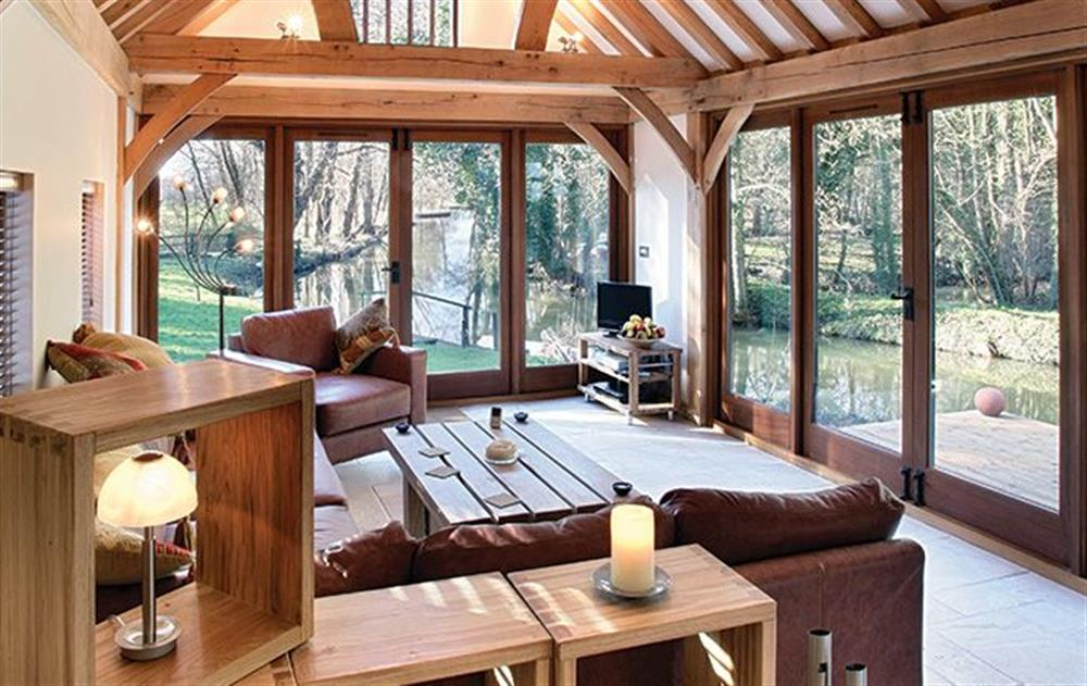 Ground floor:  Sitting area with wood burning stove at Riverside Cottage (Suffolk), Old Water Mill