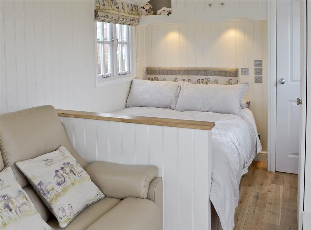 Comfortable double bed in studio style living area at The Rookery Shepherds Hut,