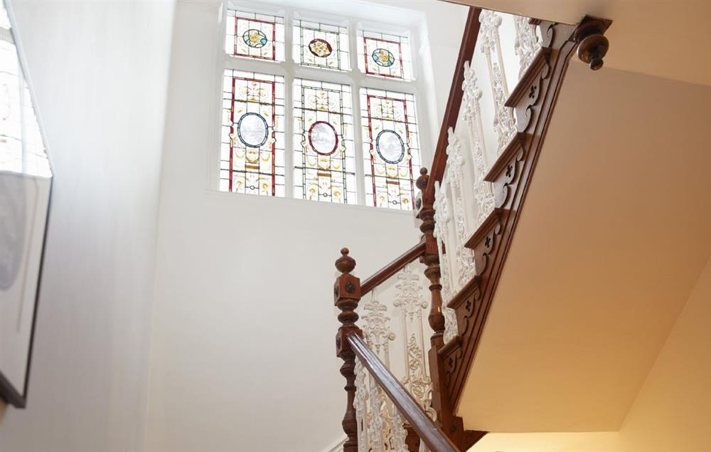 Stairway leading up to the first floor with beautiful window feature