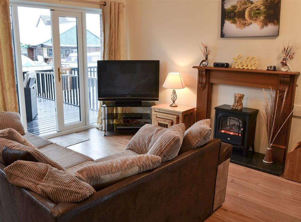 Open plan living with French doors leading to veranda at Rowans Cottage in Wroxham, Norfolk