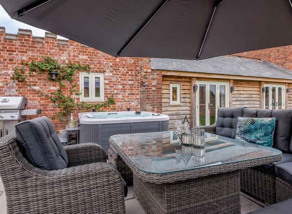 Paved patio area with outdoor furniture, BBQ and hot tub at Deer View Cottage,