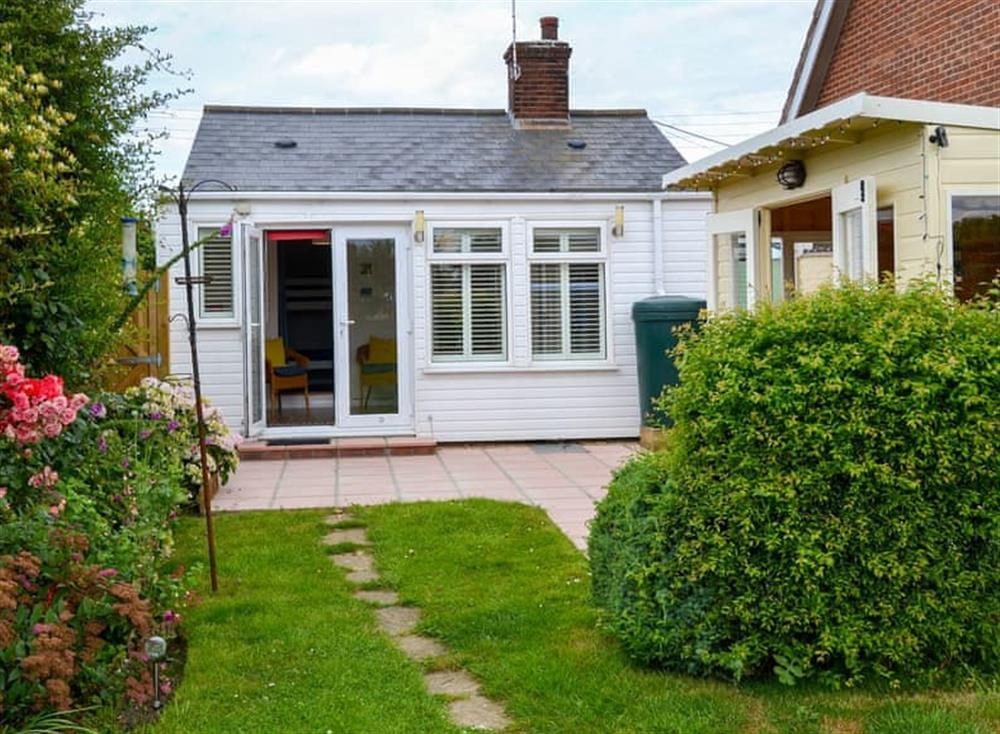 Enclosed lawned garden with patio, summerhouse and garden furniture at Sandhills in Sea Palling, Norfolk