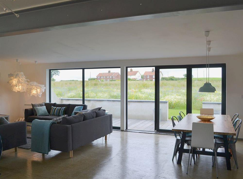 Comfortable sofas with bi-fold doors to the terrace at Seaglass Barn in East Ruston, near Stalham, Norfolk