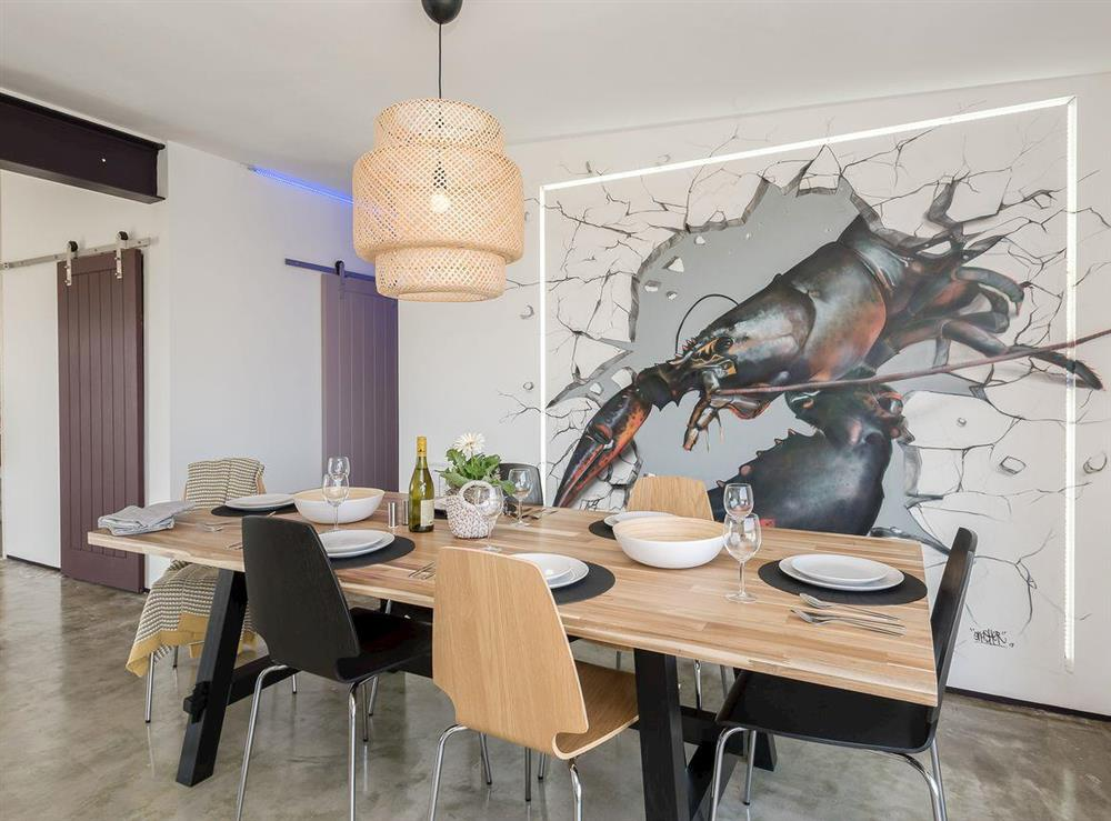 Dining area with unusual wall art at Seaglass Barn (Sand),