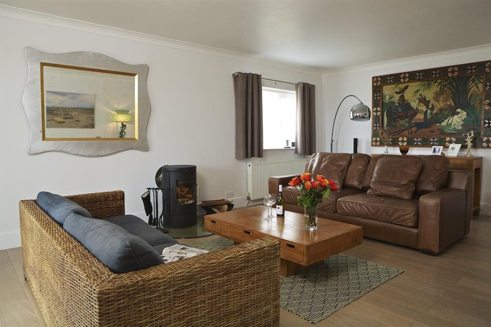 Lounge with double sofas and wood burning stove at Seaway House in , Strete