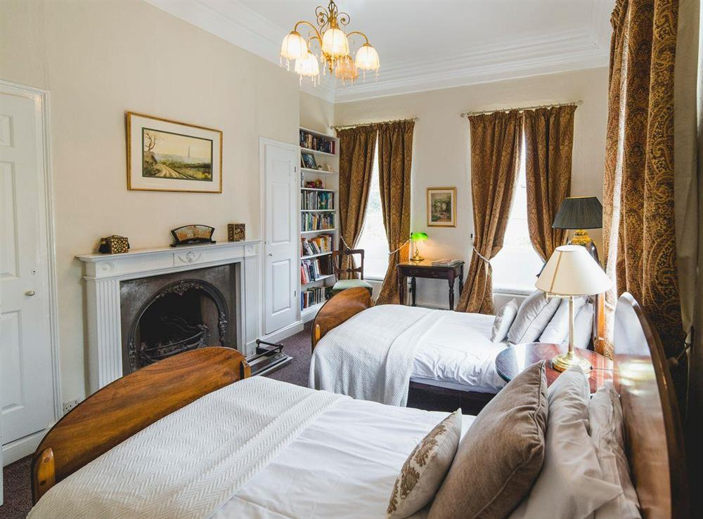 Characterful twin bedroom with feature fireplace at The Sedgeford Hall,