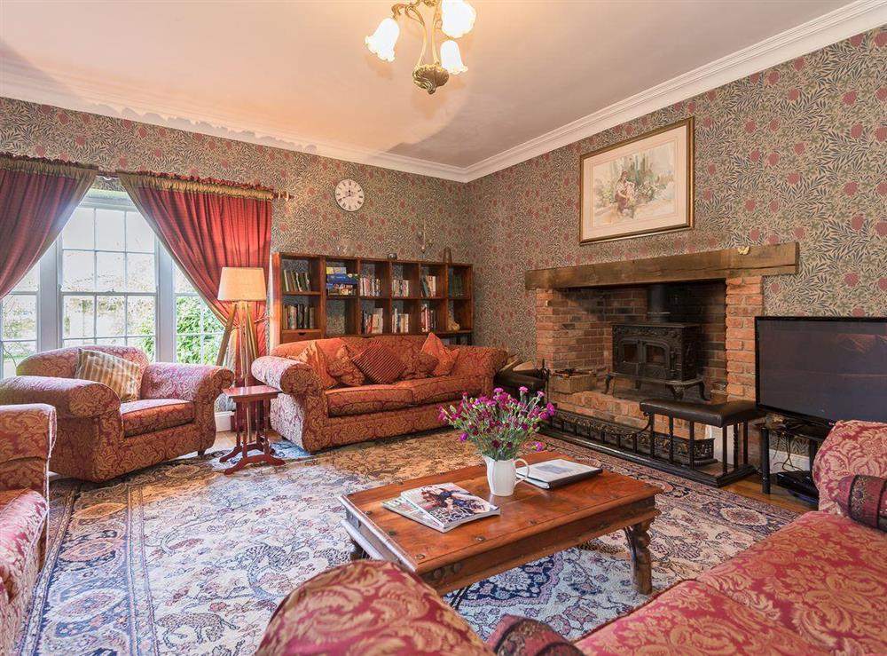 Drawing room with Inglenook fireplace & wood burning stove at The Sedgeford Hall,