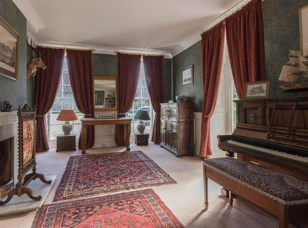 Drawing room with piano & open fire at The Sedgeford Hall,