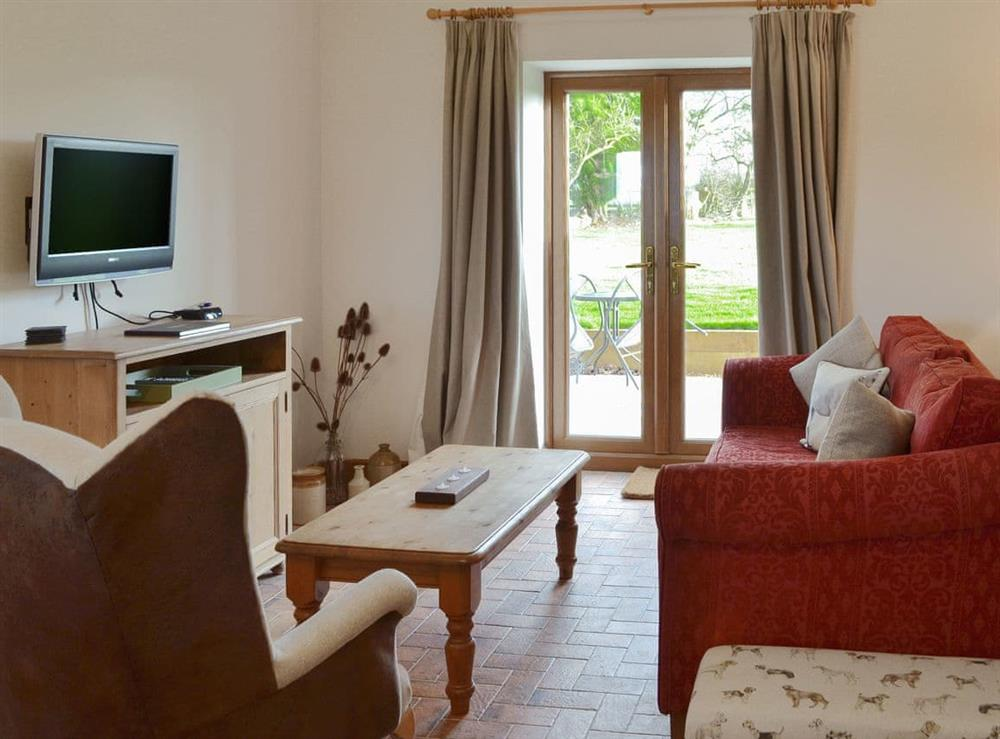 Living room with French doors leading to patio area at Shires Loft in Whitchurch, Shropshire