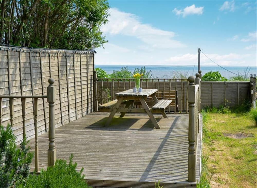 Enclosed lawned garden with patio, summerhouse and garden furniture at Smugglers Cove in Hemsby, near Caister-on-Sea, Norfolk