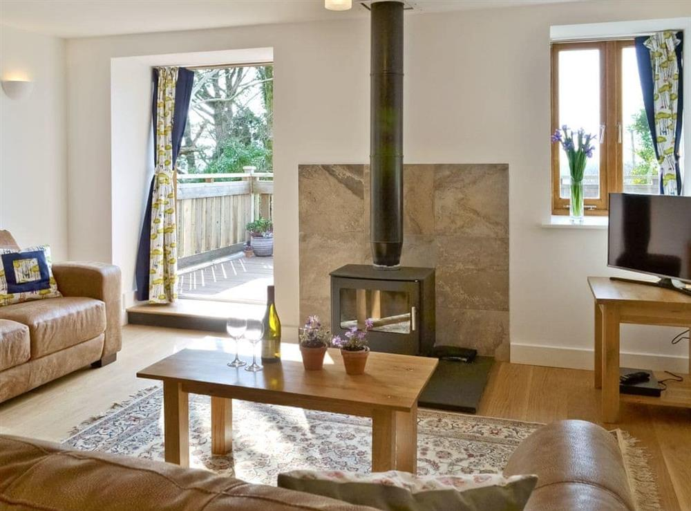 Cosy lounge with wood-burning stove and access to large balcony at Southlake Barn in Dousland, near Yelverton, Devon