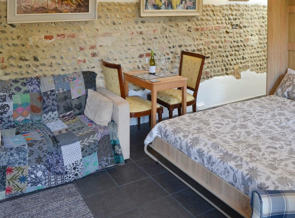 living area with un-folded double bed at The Old Stables,