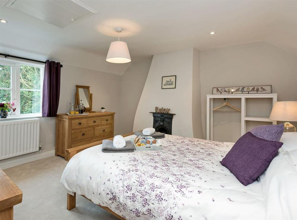 Spacious double bedroom with feature fireplace at Sunnyside in Ludham, near Wroxham, Norfolk