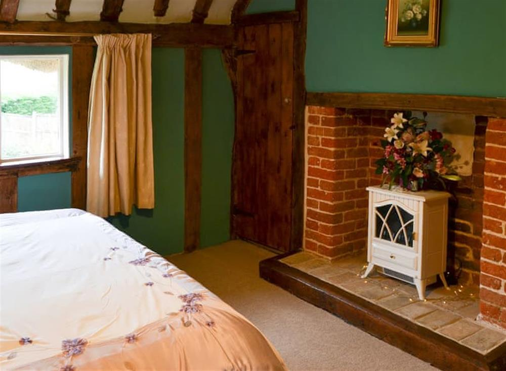 Double bedded room with feature fireplace at Tattlepot Farmhouse in Pulham Market, near Diss, Norfolk