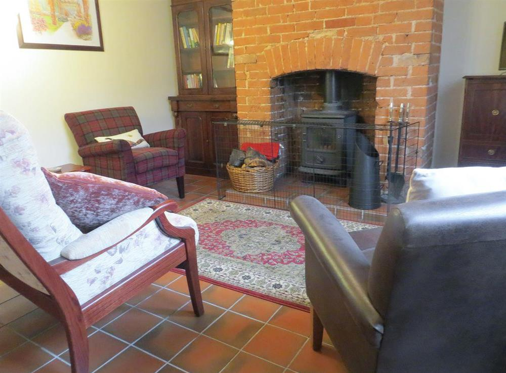 Living room with wood burner at Teapot Cottage in Helhoughton, near Fakenham, Norfolk, England