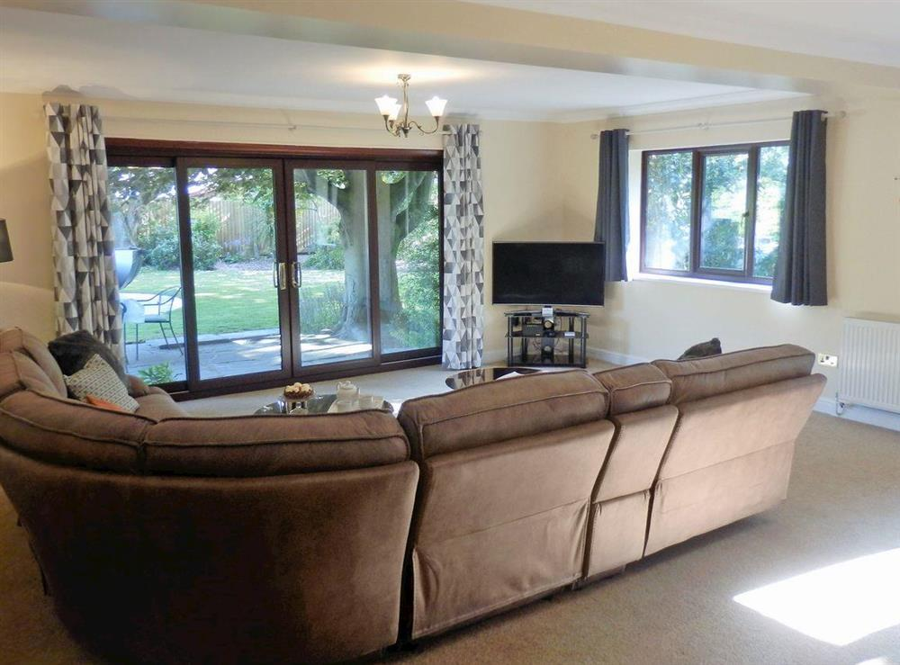 Spacious living room with patio doors to garden (photo 2) at The Beech House in Corton, near Lowestoft, Suffolk