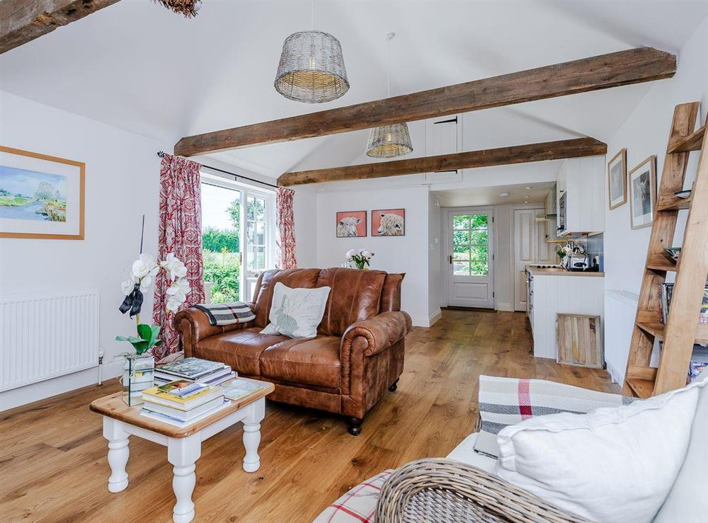 Open plan living space with wood flooring & exposed beams at The Bull Pen in Lawford, Essex, England