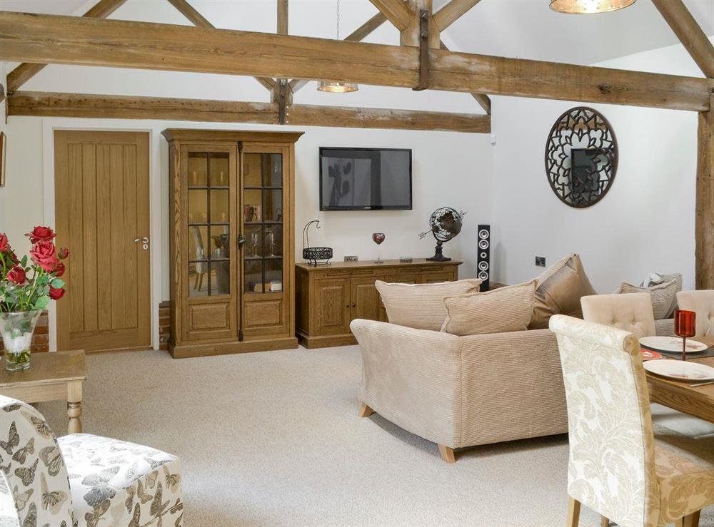 Spacious living area with exposed wood beams at The Cowshed in Horning, near Wroxham, Norfolk