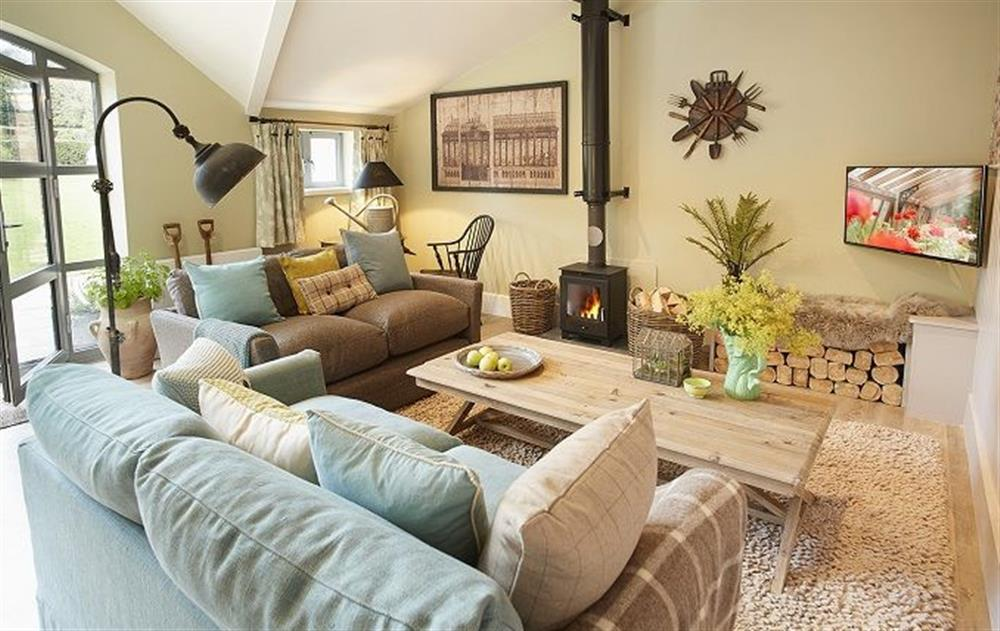 Ground floor: Open plan sitting room with wood burning stove at The Gardeners Bothy, Weston Park