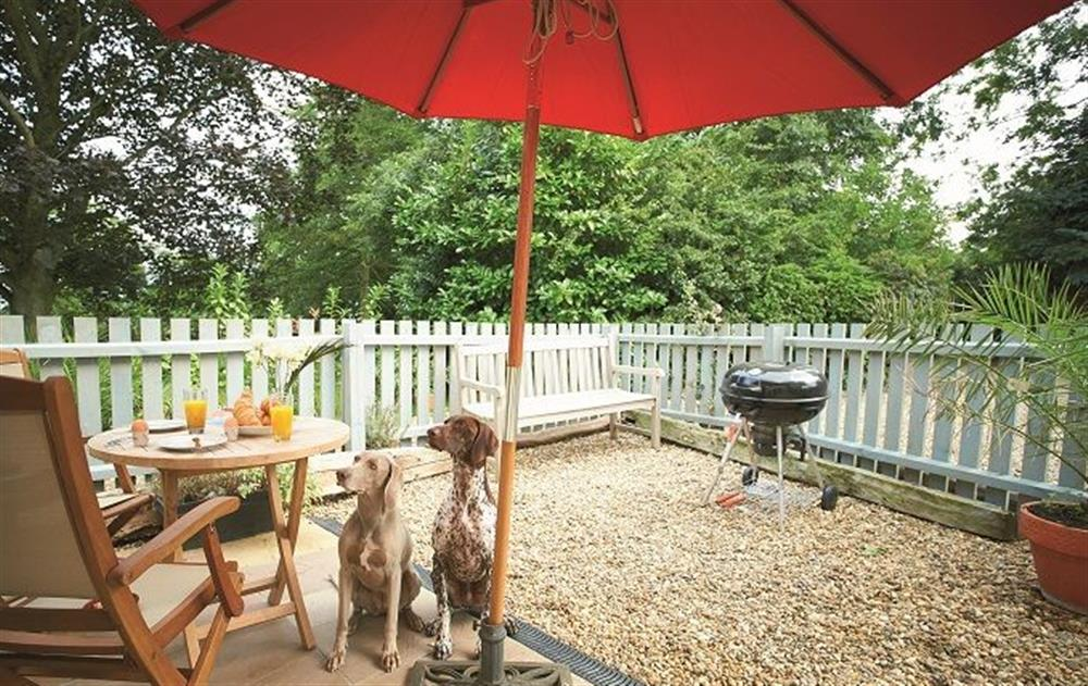 French windows open onto private enclosed and dog safe patio with table, chairs and barbecue at The Maltings, Trunch