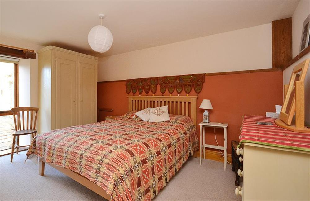The bedroom looks onto a grassed courtyard at The Old Dairy, East Allington