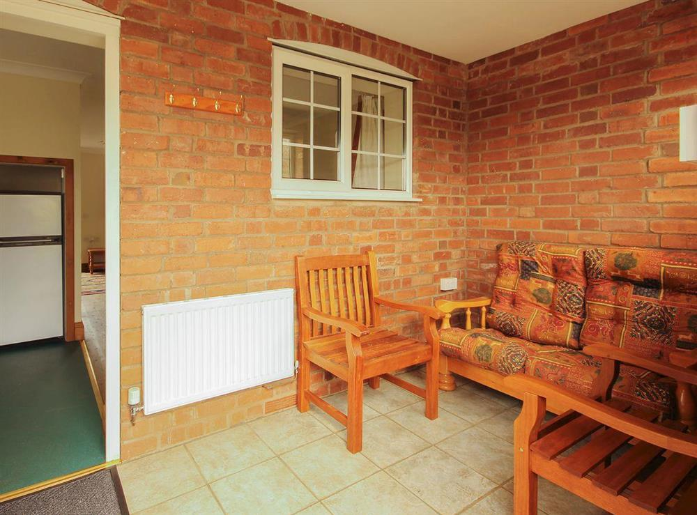 Light and airy tile-floored entrance porch with seating at Sweet Coppin,