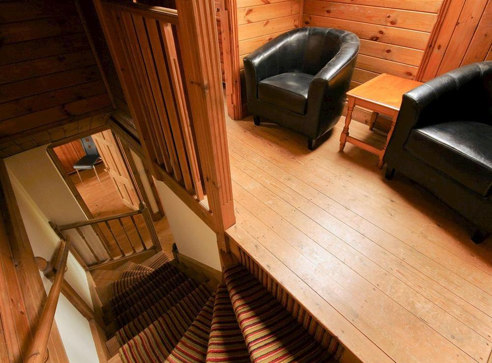 Stairs and wood-floored landing with comfortable chairs at Sweet Coppin,