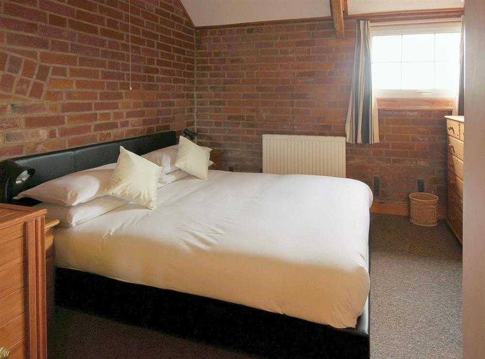 Double bedroom with exposed brick walls and sloping ceiling at Yarlington Mill,