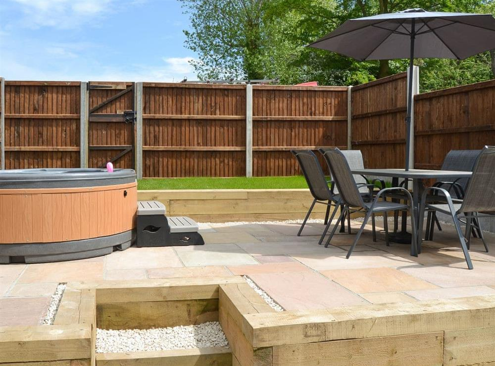 Split-level enclosed patio and garden with outdoor furniture and hot tub at The Old Stables in Swafield, near North Walsham, Norfolk