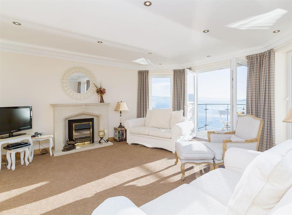 Sumptuous living/dining room with electric coal-effect fireplace at The Penthouse in Strone, near Dunoon, Argyll