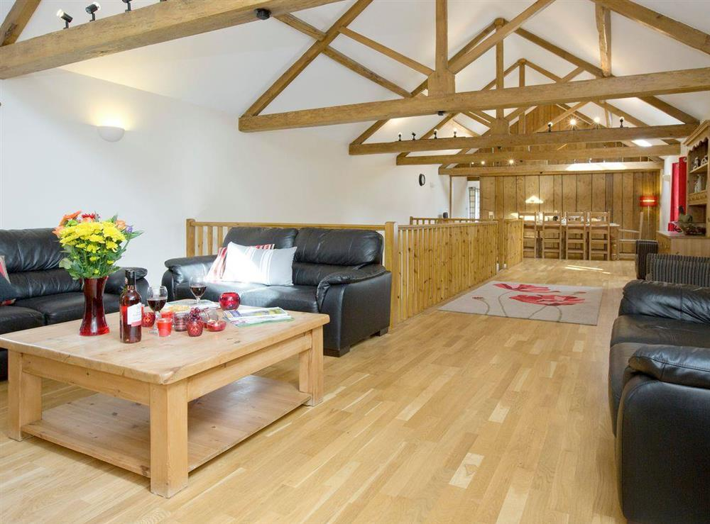 Light and airy living and dining area with exposed wooden trusses at Sycamore Cottage,
