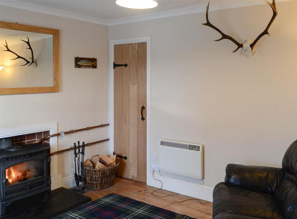 Living room with wood burner at Thistle Cottage in Bonar Bridge, near Lairg, Highlands, Ross-Shire