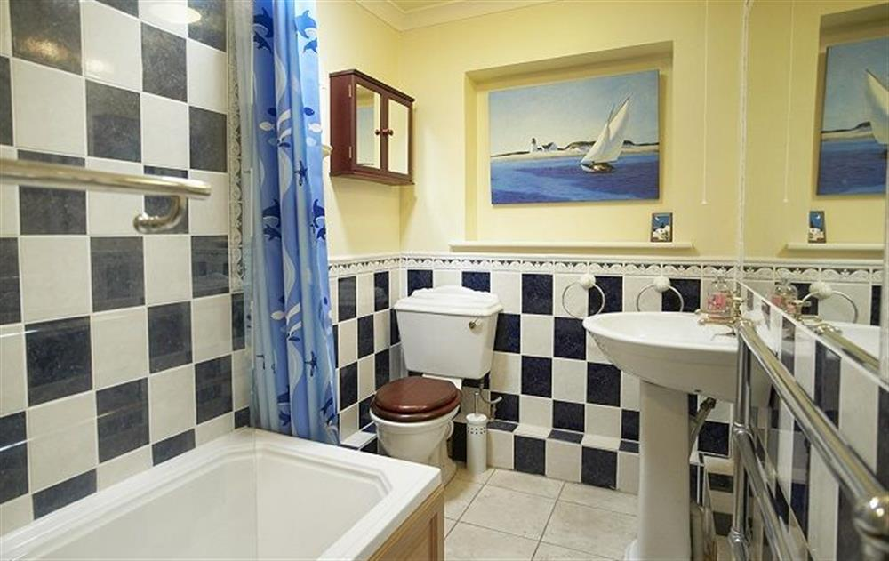 First floor: Family bathroom with bath with an electric shower and wc at Underwood House, East Knoyle