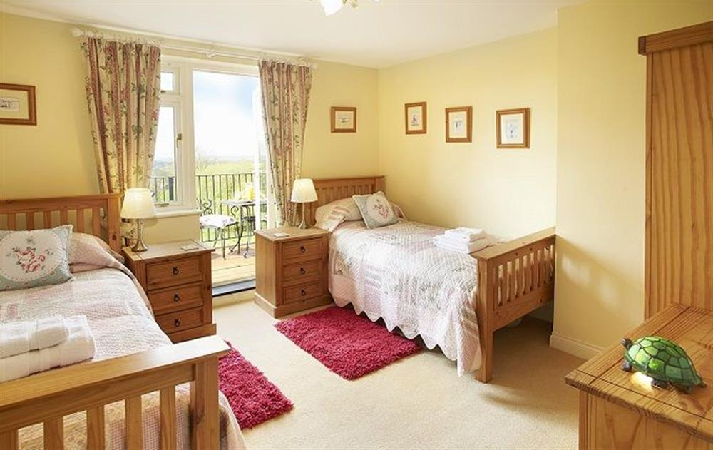 First floor: Twin bedroom with 3' beds and patio doors leading onto the balcony at Underwood House, East Knoyle