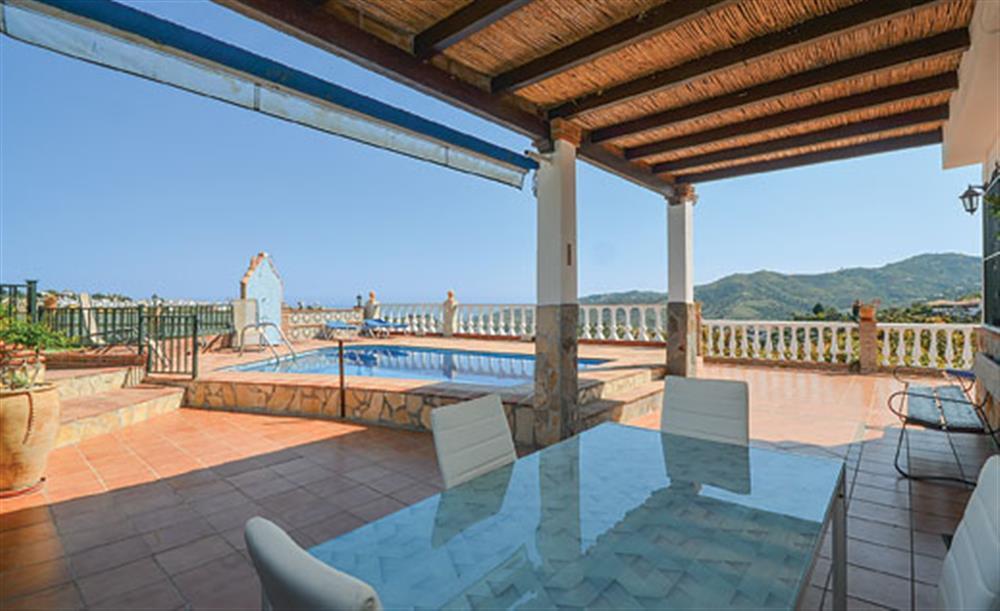 Shaded dining area and swimming pool at Villa Amparo, Frigiliana, Andalucia