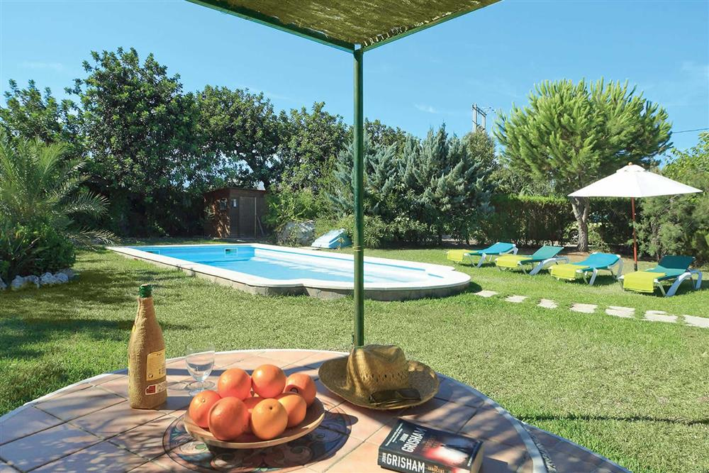 Lawned garden and pool at Villa Can Canaveret, The Balearic Islands, Spain