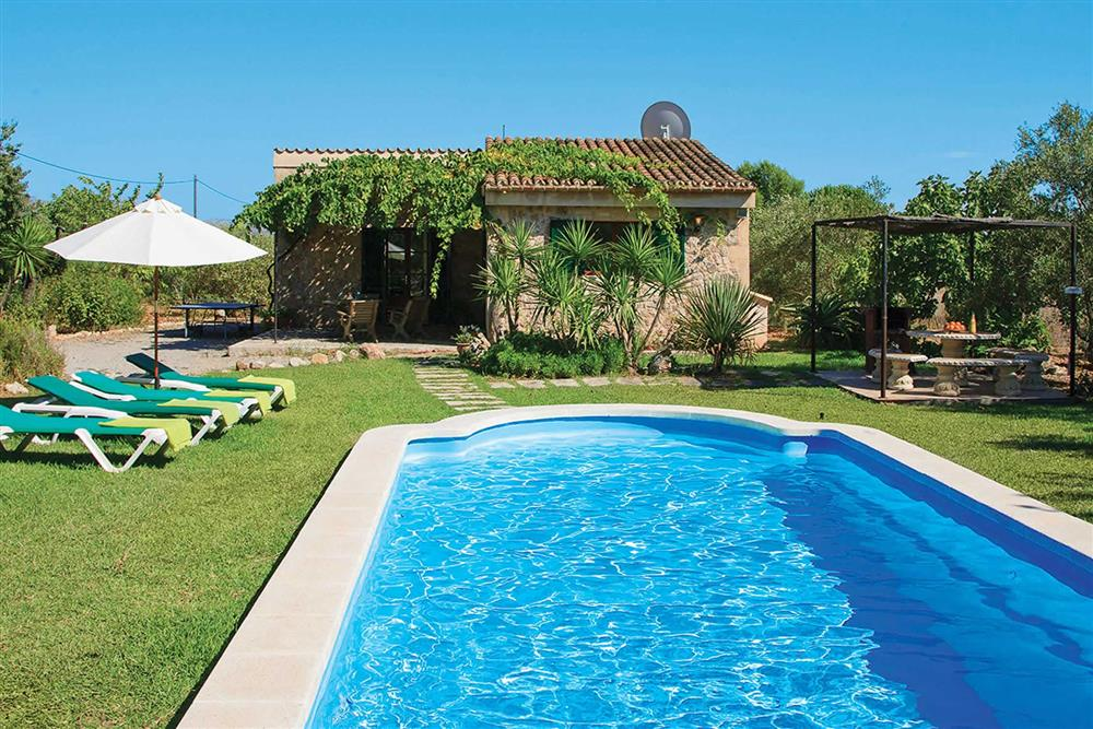 Swimming pool and garden at Villa Can Canaveret, The Balearic Islands, Spain