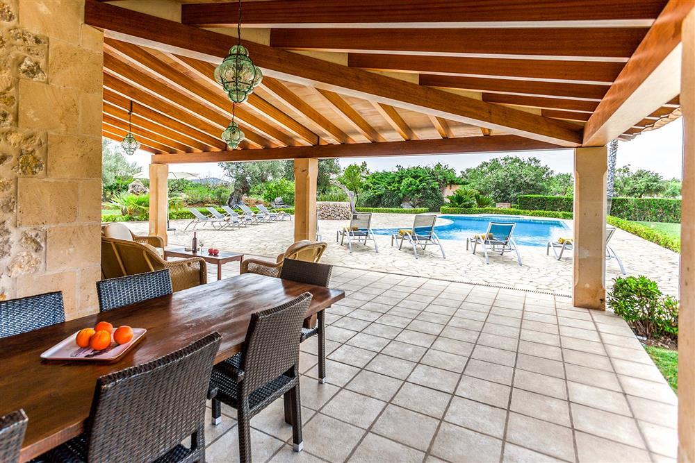 Covered terrace, alfresco dining, sunloungers at Villa Les Oliveres, Puerto Pollensa, Mallorca