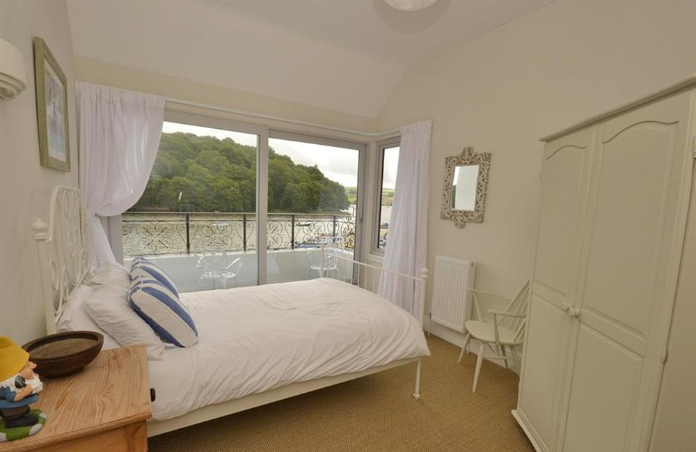 The master bedroom with patio doors to the balcony at Waters Edge, Stoke Gabriel