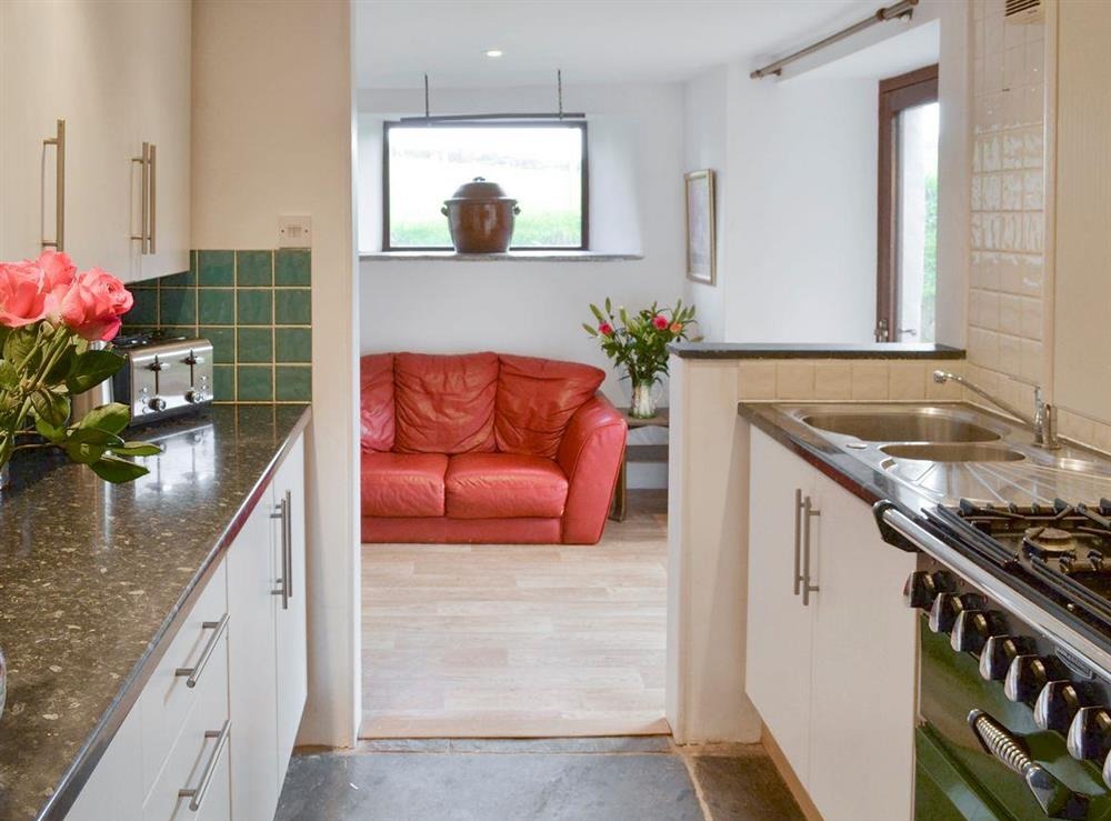 Fully-appointed kitchen with open aspect to dining room at Mad Nelly Cottage,